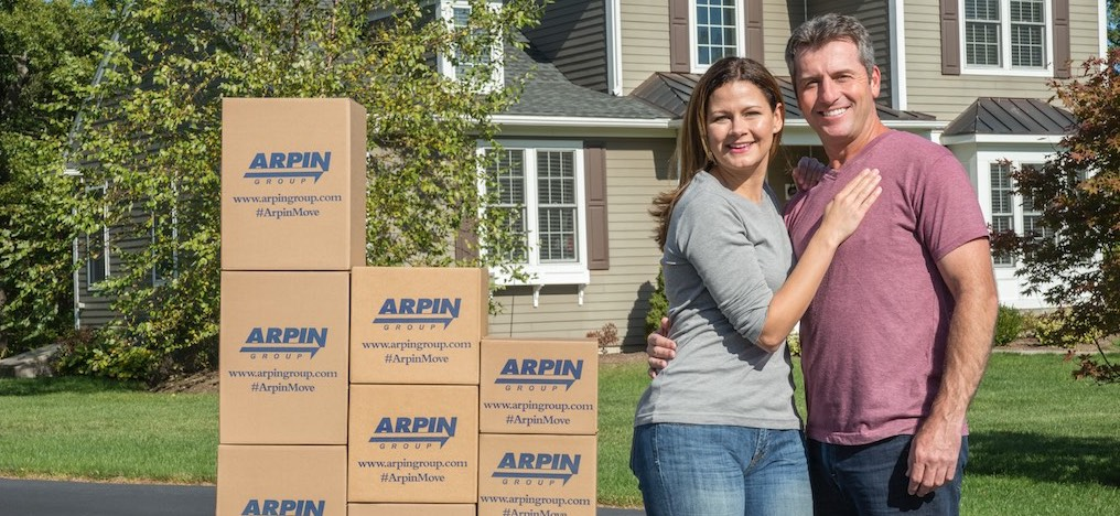 Happy couple with Arpin boxes in front of house