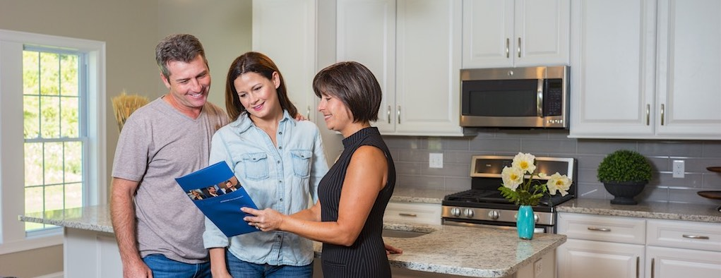 Three people going over a brochure in a kitchen
