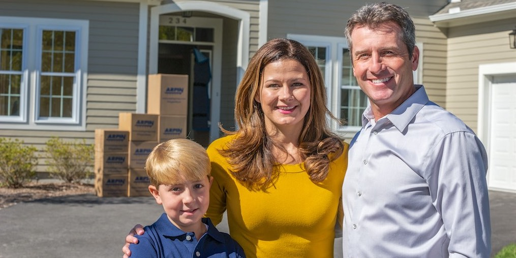 Happy couple with child in front of moving boxes and house